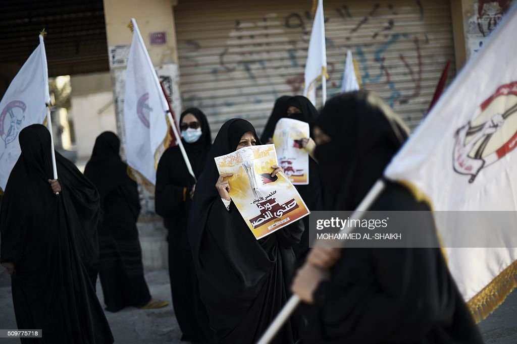 Bahraini women hold flags and posters during a demonstration to mark the fifth anniversary of the Arab Spring-inspired uprising, on February 12, 2015, in the mainly Shiite village of Sitra, south of Manama. Five years after Sunni-ruled Bahrain crushed a popular uprising by the Shiite majority, the kingdom is locked in a political impasse exacerbated by an economic crisis, analysts say. / AFP / MOHAMMED AL-SHAIKH