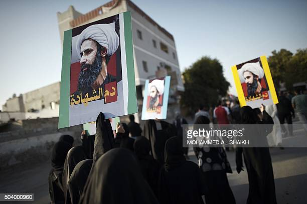 Bahraini women hold placards bearing portraits of prominent Shiite Muslim cleric Nimr alNimr during clashes with riot police in the village of Sitra...