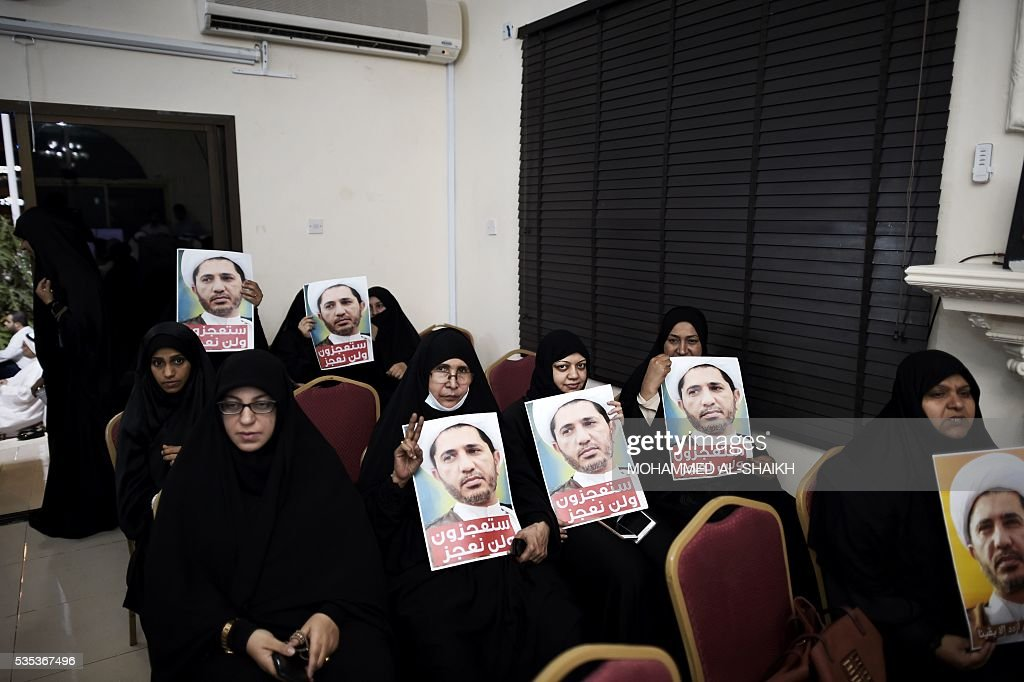 Bahraini women hold placards bearing the portrait of Sheikh Ali Salman, head of the Shiite opposition movement Al-Wefaq, during a protest on May 29, 2016 against his arrest, at Al wefaq headquarter building, in the village of Zinj on the outskirts of the capital Manama. / AFP / MOHAMMED