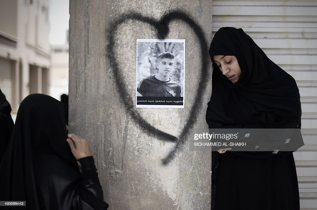Bahraini women mourn during the funeral of Sayed Mahmud Sayed Mohsin (portrait) in the village of Sitra, south of the capital Manama, on May 24, 2014. Mohsin, 15, was reportedly shot dead by security forces during an opposition protest three days ago.