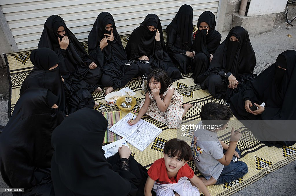 Bahraini women sit outside their home waiting for a protest to start in the village of Bilad al-Qadeem, in a suburb of Manama, on June 15, 2013. Weekly protests, that began in 2011, are held by Bahraini Shiite Muslims demanding more rights from the ruling Sunni Muslim dynasty.