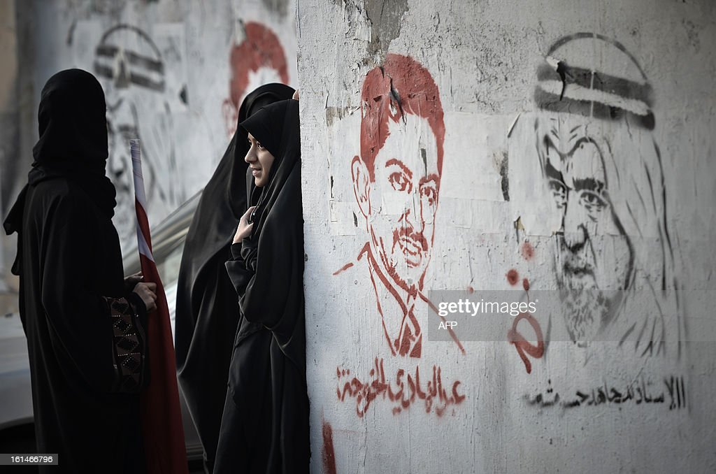 Bahraini women stand next to graffiti during an anti-government rally against the national dialogue talks on February 11, 2013, in the village of Sanabis, west of the Bahraini capital Manama. Bahrain's key political players launched a new round of talks to try to resolve the kingdom's two-year crisis, after opposition groups made a last-minute decision to join a national dialogue.