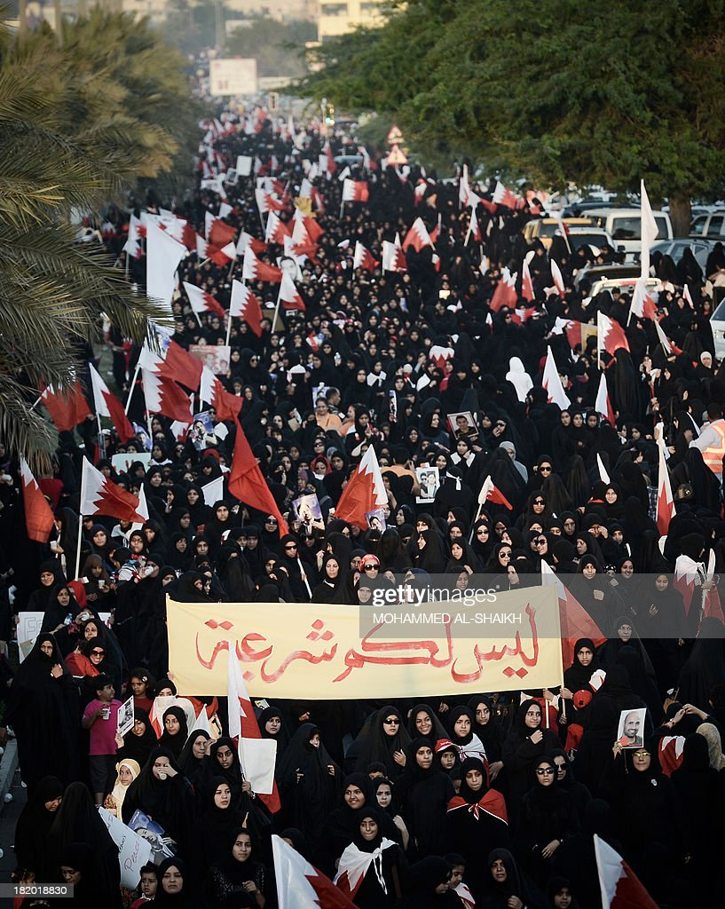 Bahraini women wave national flags and hold up a banner reading in arabic 'No legitimacy' as they take part in an anti-government protest in the village of Jannusan, west of the capital Manama, on September 27, 2013. Thousands took to the streets in Bahrain to condemn the arrest of ex-MP Marzooq, hours after clashes between protesters and police, officials and witnesses said.