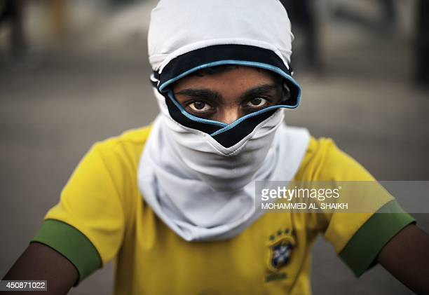 A Bahraini young boy wearing a Brazilian football team jersey poses during clashes with riot police after antigovernment protesters tried to retrieve...