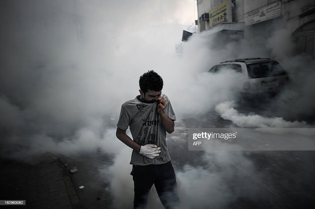 A Bahraini youth covers his face to protect himself from tear gas fired by riot police to disperse protesters who tried to reach Salmaniya hospital to retrieve the body of Mahmud al-Jaziri in the village of Zinj, a suburb of Manama, on March 2, 2013. Jaziri, 20, succumbed to his wounds on February 21 after he was shot during clashes between police and protesters marking the second anniversary of the February 14, 2011 uprising. His family says Bahraini authorities have not handed over his body because of a dispute over the location of the planned funeral.