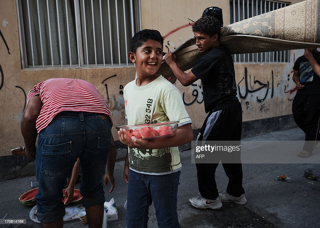 Bahraini youth pick-up the remains of a picnic prior to the start of a protest in the village of Bilad al-Qadeem, in a suburb of Manama, on June 15, 2013. Weekly protests, that began in 2011, are held by Bahraini Shiite Muslims demanding more rights from the ruling Sunni Muslim dynasty.