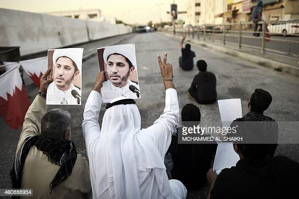 Bahrainis hold up portraits of the head of the banned Shiite opposition movement AlWefaq Sheikh Ali Salman during clashes with riot police following...