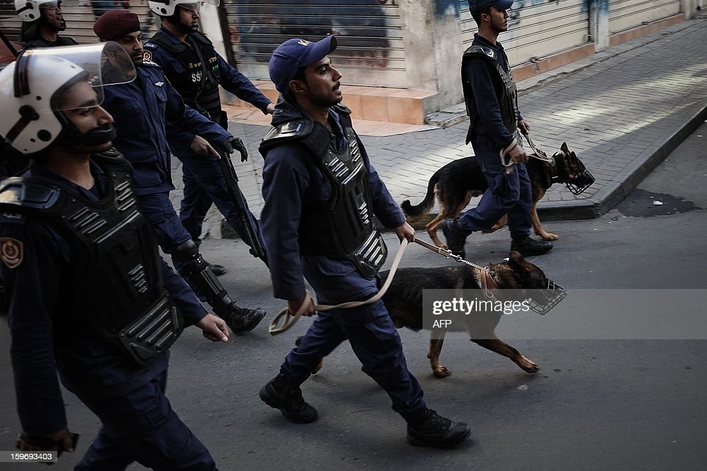 Bahrain's Police forces walk with bloodhounds to disperse protestors during a demonstration called for by the February 14 Youth Coalition, an Internet group that regularly calls for protests in the Shiite-majority kingdom on January 18, 2013 in the capital Manama. Bahrain's government said the demonstration had not been authorised and warned security forces would prevent it from going ahead. AFP PHOTO/MOHAMMED ALSHAIKH