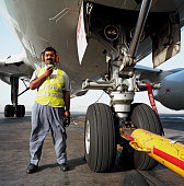 A Bahrani aircraft mechanic stands beneath the giant nose wheel assembly of a Being airliner at Bahrain International Airport Wearing a red headset...