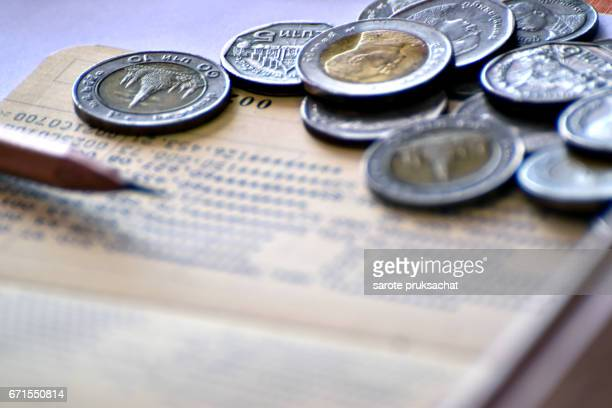 Baht coins, deposit accounts, pen, concept of saving money.