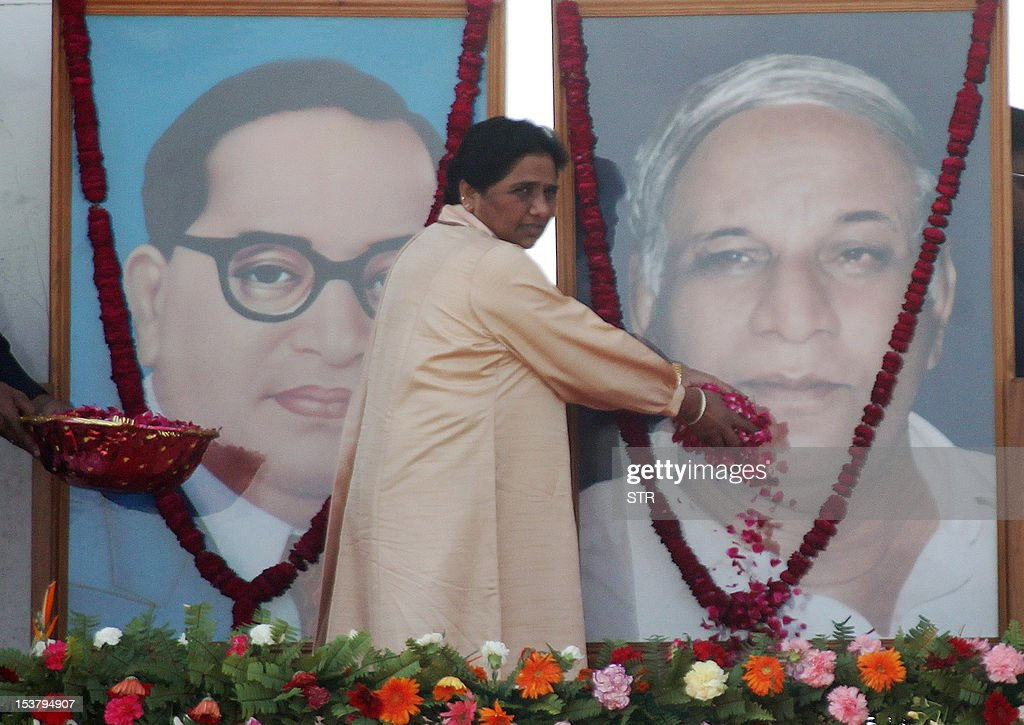 Bahujan Samaj Party (BSP) supremo Mayawati offers flowers to a photograph of party founder Kanshiram during a rally commemorating his sixth death anniversary in Lucknow on October 9, 2012. Attacking the UPA government on several fronts, BSP supremo Mayawati said her party will take a call on whether to continue its outside support to the Centre, according to the Press Trust of India.