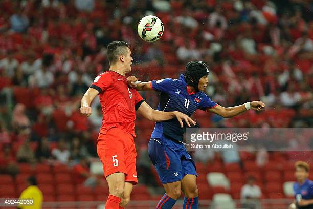 Baihakki Khaizan of Singapore and Chan Vathanaka of Cambodia challenge for the ball during the 2018 FIFA World Cup Qualifier Group E Match between...