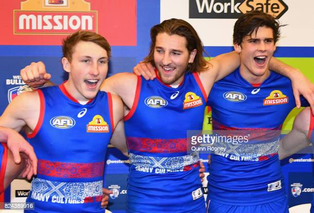 Bailey Dale Marcus Bontempelli and Lewis Young of the Bulldogs sing the song in the rooms after winning the round 19 AFL match between the Western...