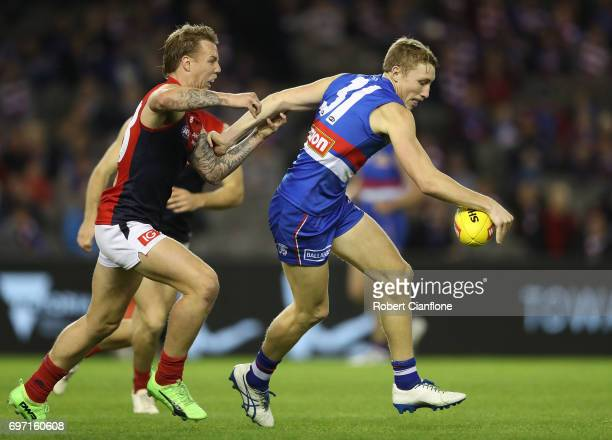 Bailey Dale of the Bulldogs is challenged by James Harmes of the Demons during the round 13 AFL match between the Western Bulldogs and the Melbourne...