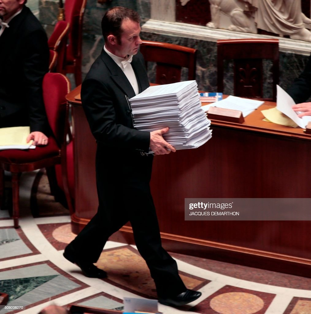 A bailiff brings copies of amendments to be debated at the French National Assembly in Paris on February 9, 2016, as French lawmakers examined proposed changes to the constitution. France's lower house of parliament is to vote on plans to enshrine a state of emergency into the constitution, including a controversial measure to strip French nationality from those convicted of terrorism and serious crimes. / AFP / JACQUES DEMARTHON