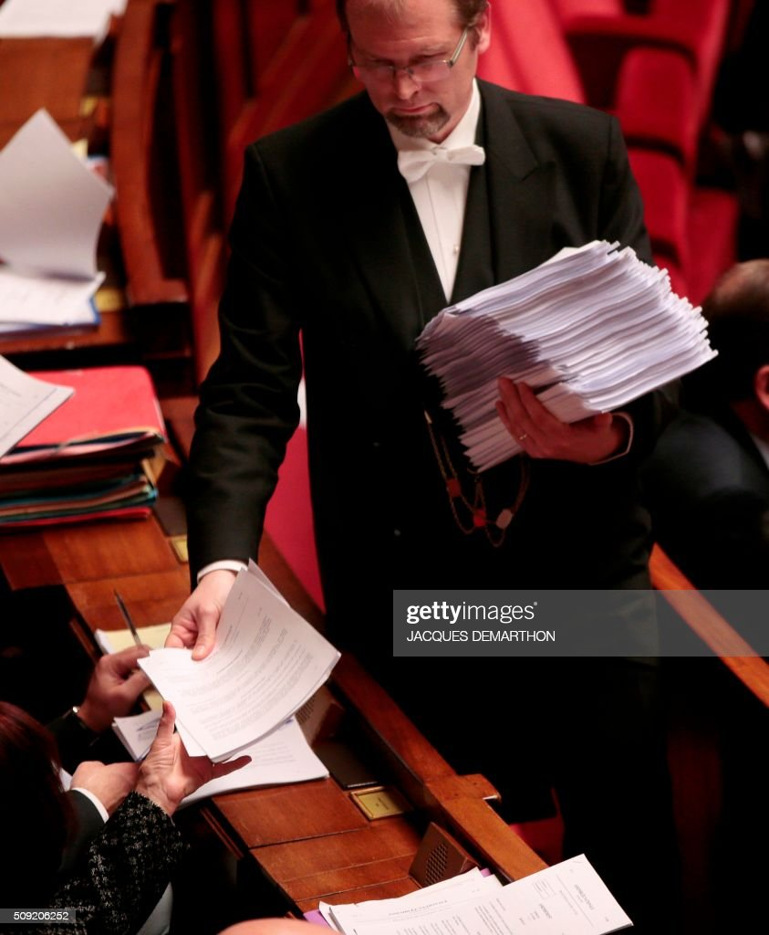 A bailiff hands out copies of amendments to be debated to MPs at the French National Assembly in Paris on February 9, 2016, as French lawmakers examined proposed changes to the constitution. France's lower house of parliament is to vote on plans to enshrine a state of emergency into the constitution, including a controversial measure to strip French nationality from those convicted of terrorism and serious crimes. / AFP / JACQUES DEMARTHON
