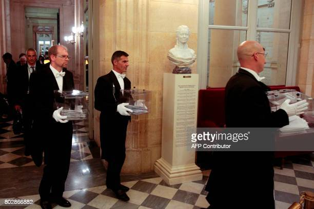 Bailiffs carry ballot boxes after a vote during a session at the National Assembly in Paris on June 28 one day after the inaugural session of the...