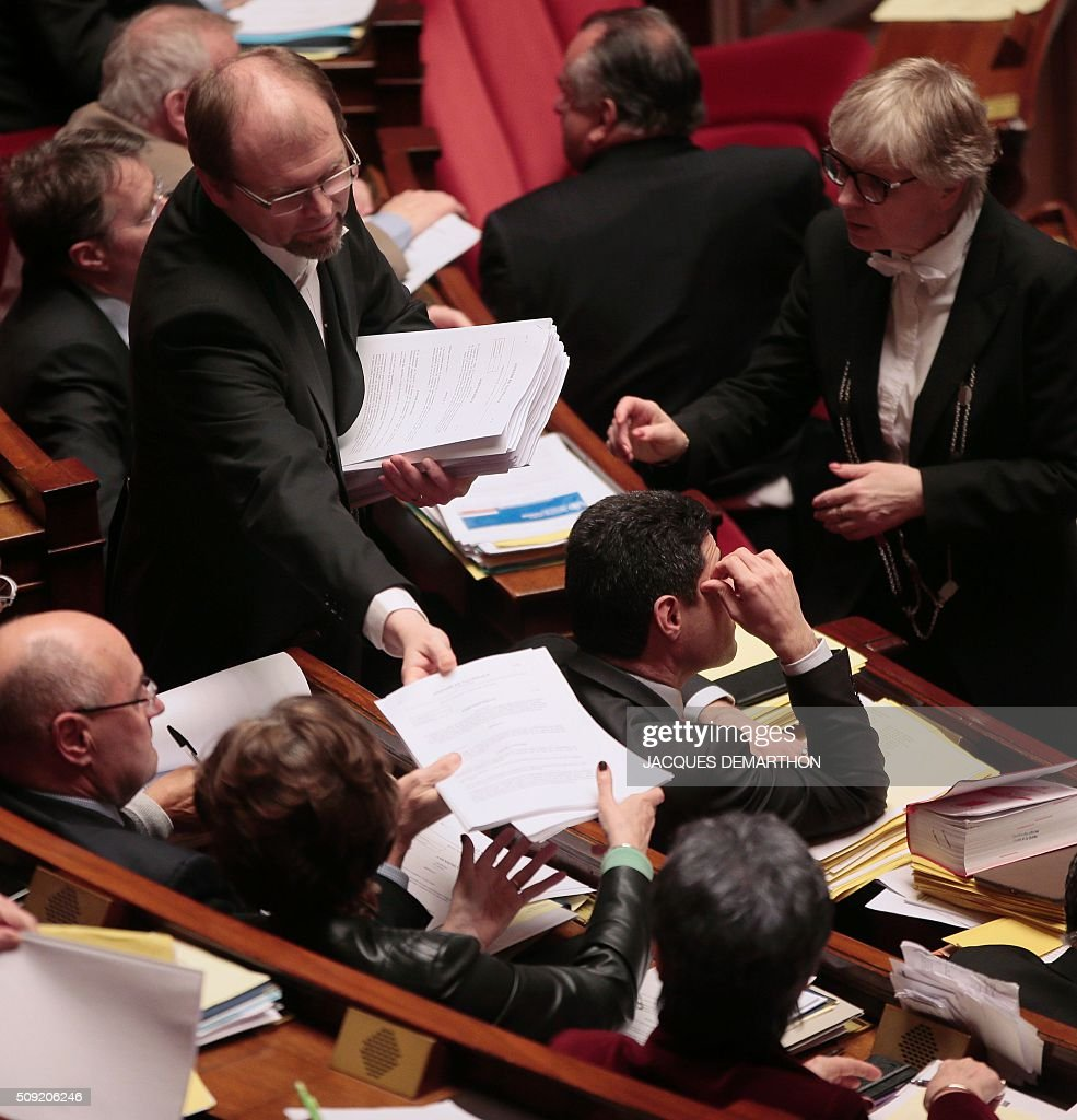Bailiffs hand out copies of amendments to be debated to MPs at the French National Assembly in Paris on February 9, 2016, as French lawmakers examined proposed changes to the constitution. France's lower house of parliament is to vote on plans to enshrine a state of emergency into the constitution, including a controversial measure to strip French nationality from those convicted of terrorism and serious crimes. / AFP / JACQUES DEMARTHON