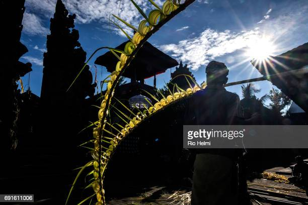 Bainese man works with palm fronds on a 'penjor' decorated bamboo pole used for celebrations in preparation for a temple ceremony in Bayad Tegallalang