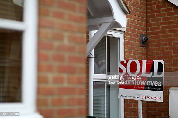 A Bairstow Eves estate agent's 'Sold' sign stands outside the window of a house on a residential housing estate in Chafford Hundred UK on Tuesday...