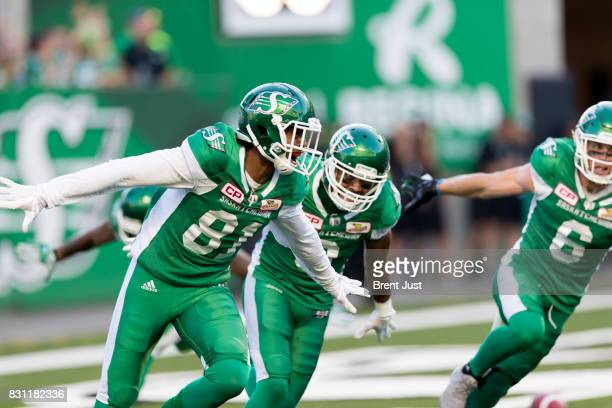 Bakari Grant Nic Demski and Rob Bagg of the Saskatchewan Roughriders celebrate after Grant scored a touchdown in the first half of the game between...