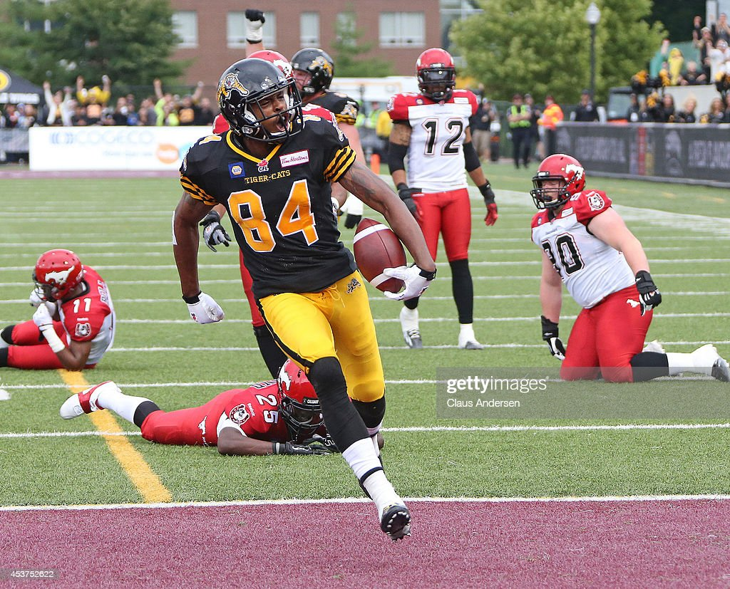 Bakari Grant of the Hamilton TigerCats celebrates a touchdown against the Calgary Stampeders in a CFL game at Ron Joyce Stadium on August 16 2014 in...