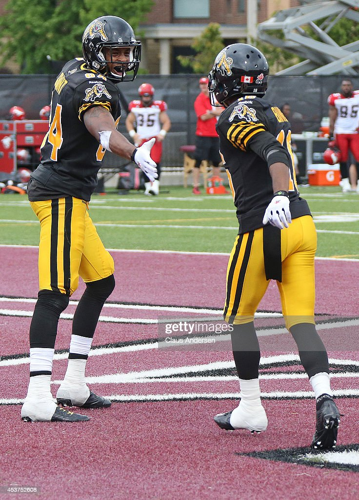 Bakari Grant of the Hamilton TigerCats celebrates a touchdown with teammate Brandon banks against the Calgary Stampeders in a CFL game at Ron Joyce...