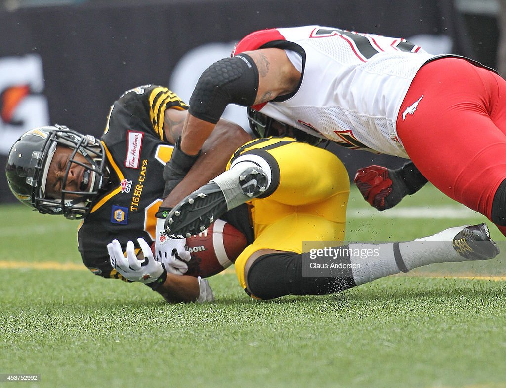 Bakari Grant of the Hamilton TigerCats is taken down hard against the Calgary Stampeders in a CFL game at Ron Joyce Stadium on August 16 2014 in...