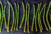 Baked asparagus on a dark background.