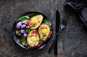 Baked avocado with egg and bacon ,flat lay on dark textured  background
