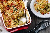 Baked brussel sprout gratin with a bacon and bread crumbs on wooden background