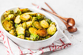 Baked brussels sprouts on a white plate. Plant based diet concept.