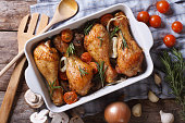 Baked chicken legs with vegetables close-up. horizontal view from above