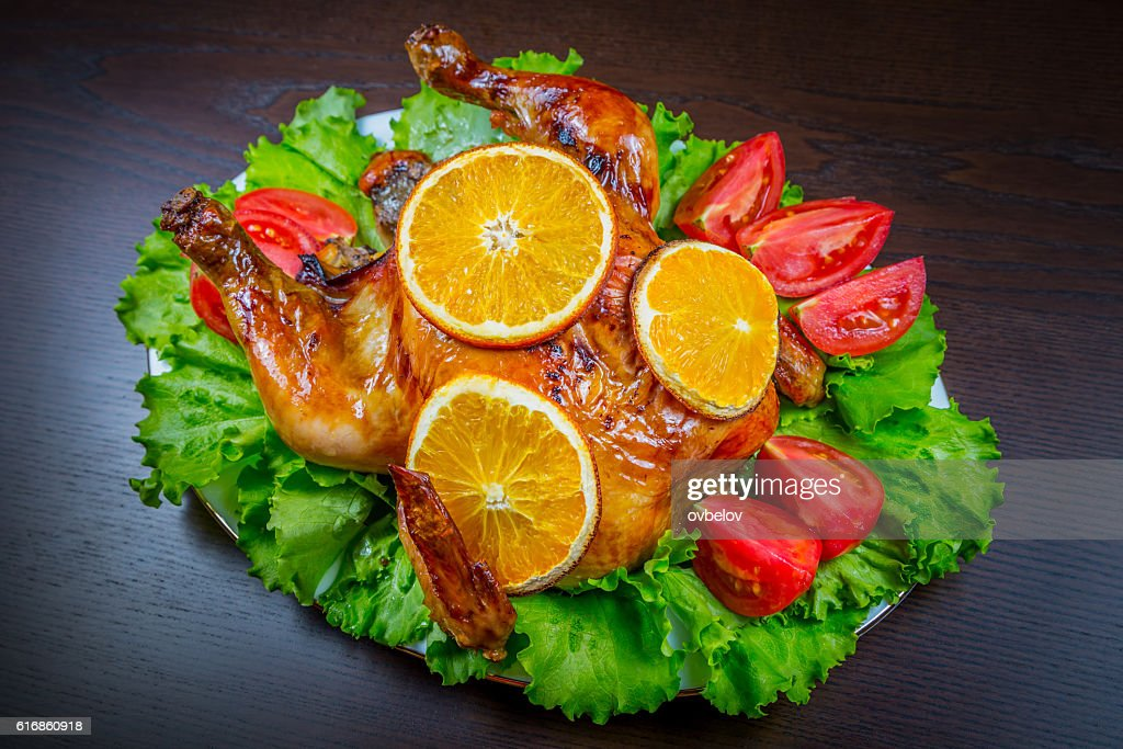Baked chicken with oranges and fresh tomatoes : Stock Photo
