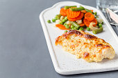 Baked cod fish fillet under cheese, mustard, pepper and cream crust, served with steamed vegetables, on a ceramic board, horizontal, copy space