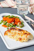 Baked cod fish fillet under cheese, mustard, pepper and cream crust, served with steamed vegetables, on a ceramic board, vertical