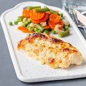 Baked cod fish fillet under cheese, mustard, pepper and cream crust, served with steamed vegetables, on ceramic board, square format
