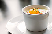 Baked egg with chive and pepper in ramekin.