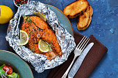 Baked in a foil steak salmon with a lemon and a marble on a wooden background.