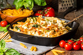 Baked pasta with broccoli, cauliflower, cheese and bechamel sauce in a frying pan on wooden bachfround