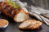 Baked pork loin with whole grain mustard served on black slate