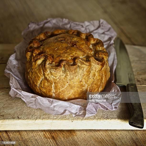 Baked pork pie on wooden board