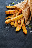 Baked potato wedges  with addition sea salt and rosemary on a black background, top view