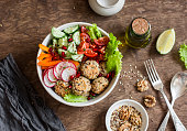 Baked quinoa meatballs and vegetable salad on a wooden table, top view.  Buddha bowl. Healthy, diet, vegetarian food concept. Flat lay