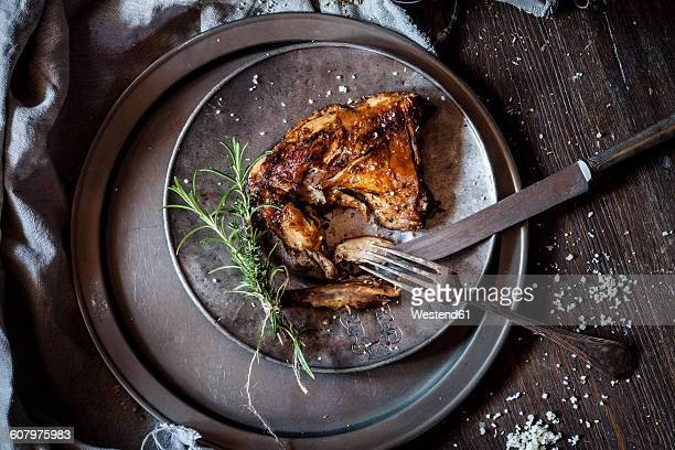 Baked rabbit legs on plate, thyme, rosemary and salt