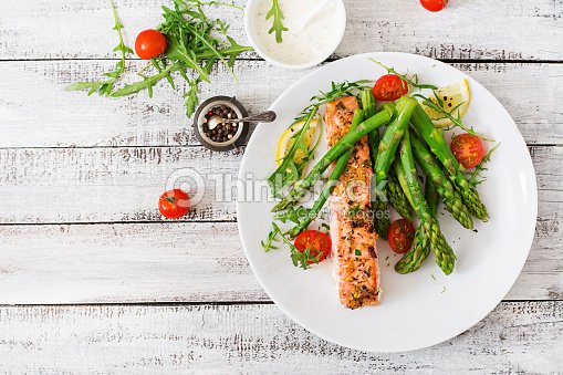 Baked salmon garnished with asparagus and tomatoes with herbs : Stock Photo