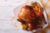 baked whole chicken with oranges and potatoes on a plate. horizontal view from above