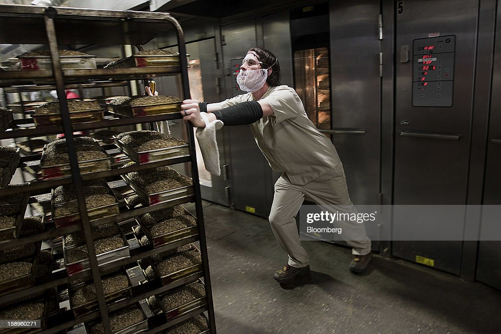 Baker Adam Vandercoevering pushes a cart of bread into an oven at Dave's Killer Bread bakery in Milwaukie, Oregon, U.S., on Friday, Jan. 4, 2013. Goode Partners, a private equity firm specializing in growth investments in the branded consumer products sectors, has purchased a fifty percent stake in Dave's Killer Bread which will help the company expand into new markets around the country. Photographer: Natalie Behring/Bloomberg via Getty Images