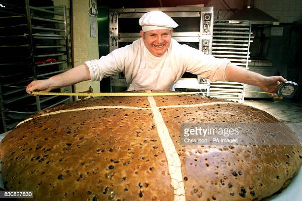 Baker Brian Collins measures his record attempt to beat the record for the world's largest hot cross bun at Pegrum's Bakery in Rustington East Sussex...