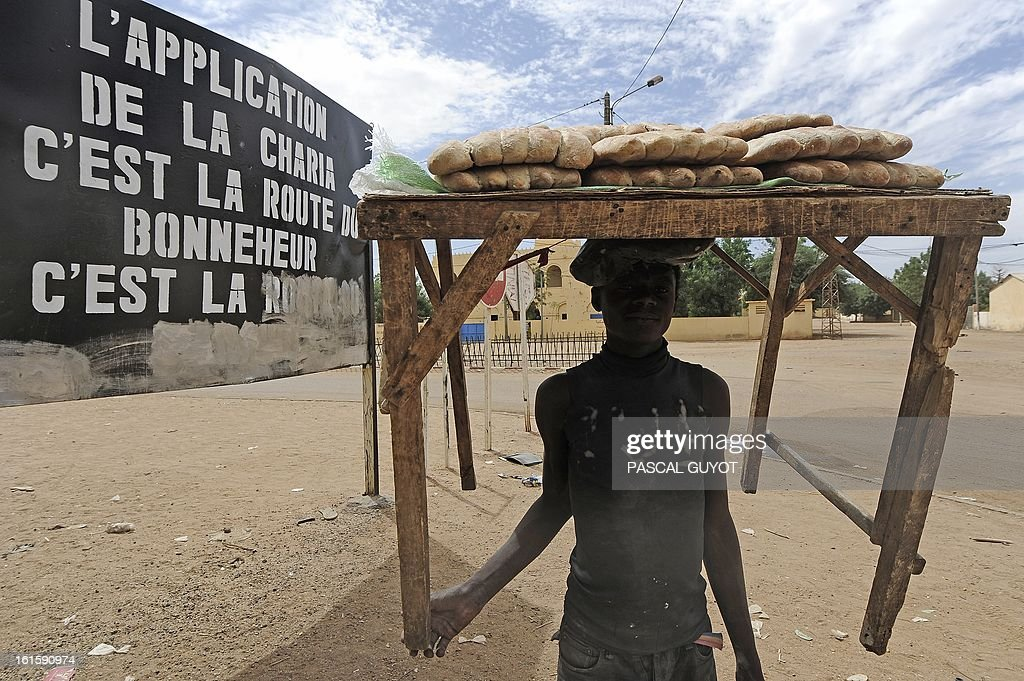 A baker carries bread on February 12, 2013 in the center of the northern Malian city of Gao, where the militant group Movement for Oneness and Jihad in West Africa (MUJAO) had controlled the city since June until the troops arrived in late January. African and French troops were on alert on February 12 after the MUJAO claimed a February 10 guerrilla attack and a pair of suicide bombings on February 8 and 9. Billboard reads: 'Enforcement of Sharia is the road to happiness.' GUYOT